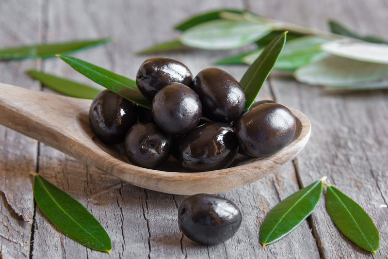 Fresh black olives on a wooden spoon