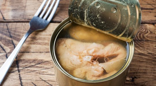 Open tin can with pink salmon fish on wooden background.