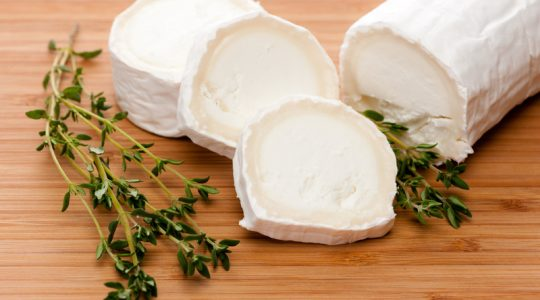 Slices of Goat cheese with fresh thyme on a Bamboo Cutting board.